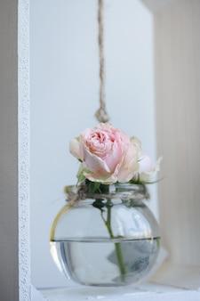 Vaso de vidro com pequena flor rosa em fundo cinza amarelo objeto antigo de decoração de interiores