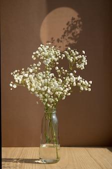 Vaso de vidro minimalista com flores brancas secas em fundo marrom elegante e minimalista ...