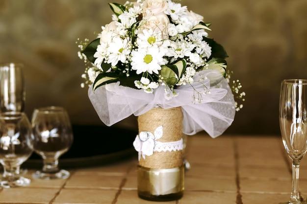 Vaso decorativo bonito com buquê luxuriante de margaridas e rosas e vegetação sobre a mesa entre os copos de champanhe e conhaque.