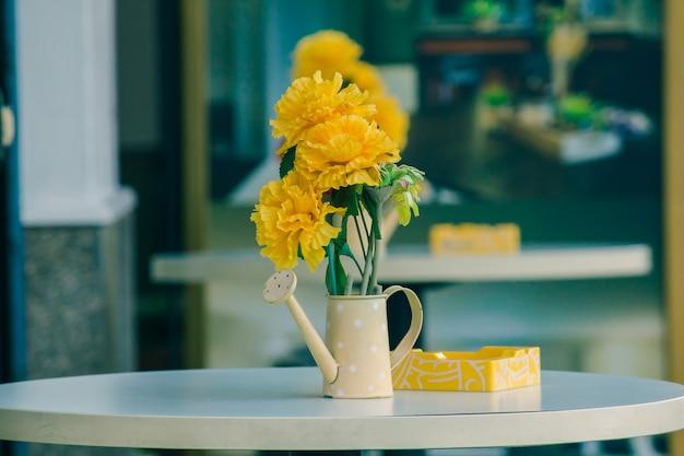 Vaso, potes, regadores em uma mesa branca