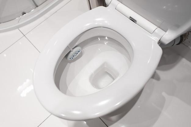 Vaso sanitário de cerâmica branca no banheiro