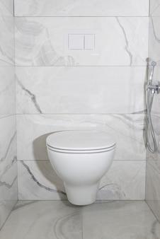 Vaso sanitário suspenso com azulejos cinza. o interior do banheiro após a renovação.