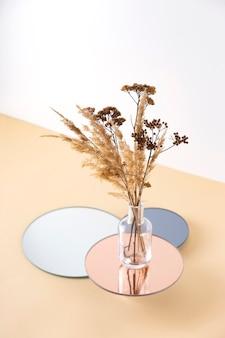 Vaso transparente com flores secas em suportes espelhados