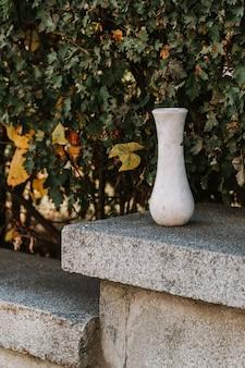 Vaso vazio de mármore em fundo de folhas verdes ao ar livre