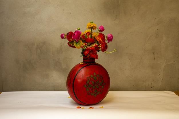Vaso vermelho vintage com peônias vermelhas e laranja em frente a uma parede velha