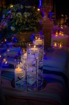 Vasos altos com água e velas no topo