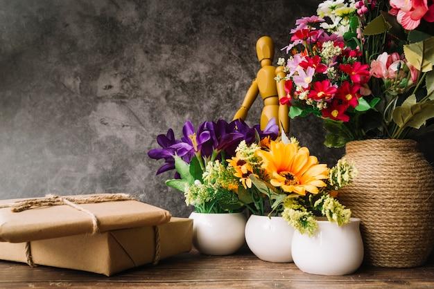 Vasos de flores com boneco de madeira e caixas de presente na mesa de madeira