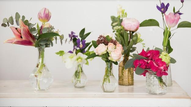 Vasos de flores frescas na mesa contra o pano de fundo branco
