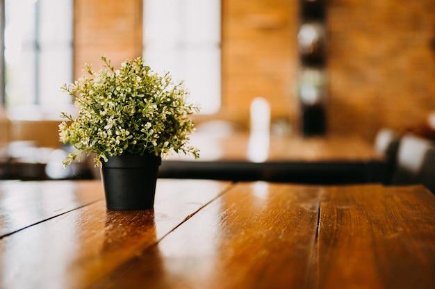 Vasos de flores pretos colocados em uma mesa de madeira em uma loja de café