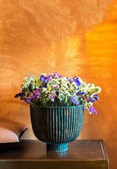 Vasos de flores verdes em mesas de madeira e em paredes laranja