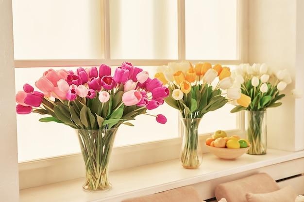Vasos de tulipas artificiais em vasos na janela