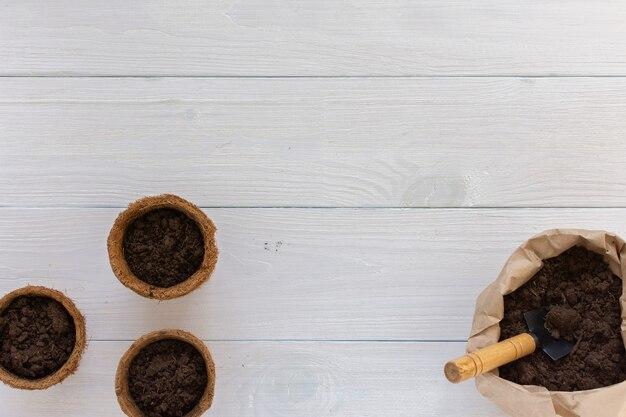 Vasos ecológicos para mudas em fundo branco de madeira, saquinho com espátula de terra e jardim