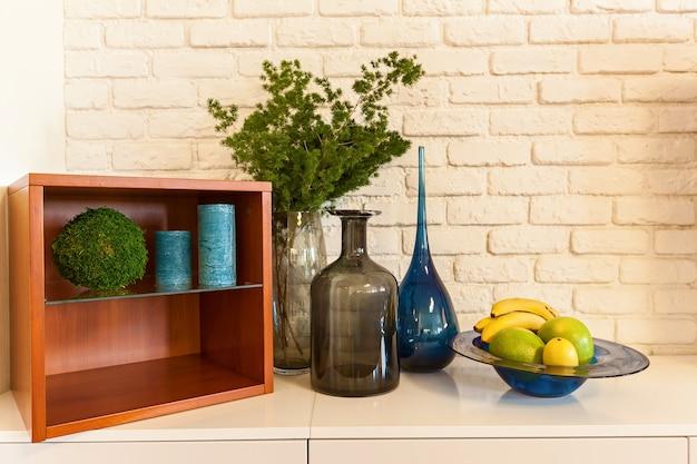 Vasos flores frutas mesa de cabeceira sobre uma mesa no fundo de uma parede de cerâmica branca