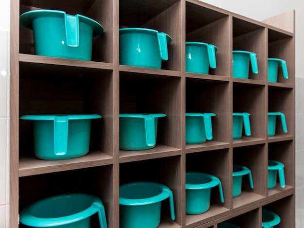 Vasos turquesa para crianças enfileirados em uma prateleira no jardim de infância