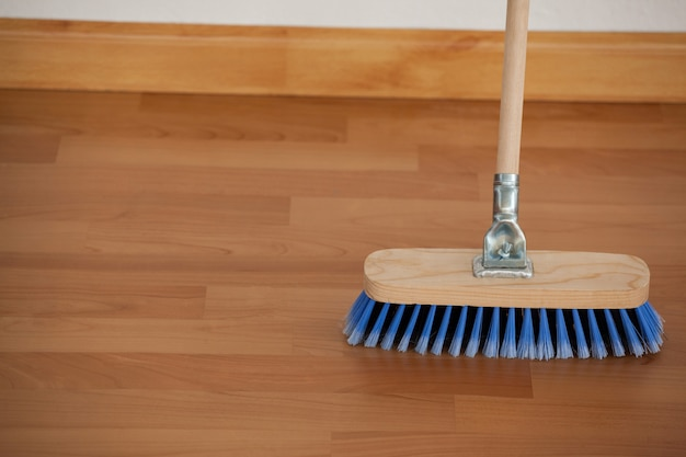 Vassoura arrebatadora com cabo de madeira no chão