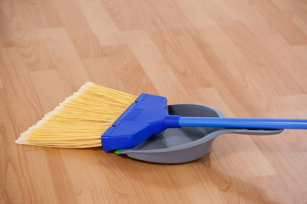 Vassoura arrebatadora com pá no chão de madeira
