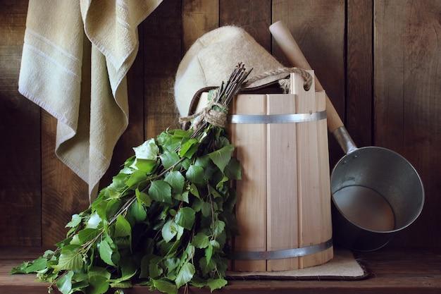 Vassoura de banho feita de bétula e balde de madeira em um banho russo