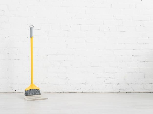 Vassoura de limpeza com parede de tijolos brancos