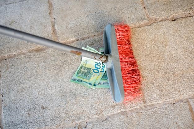 Vassoura de limpeza varrendo notas de centésimo euro na rua