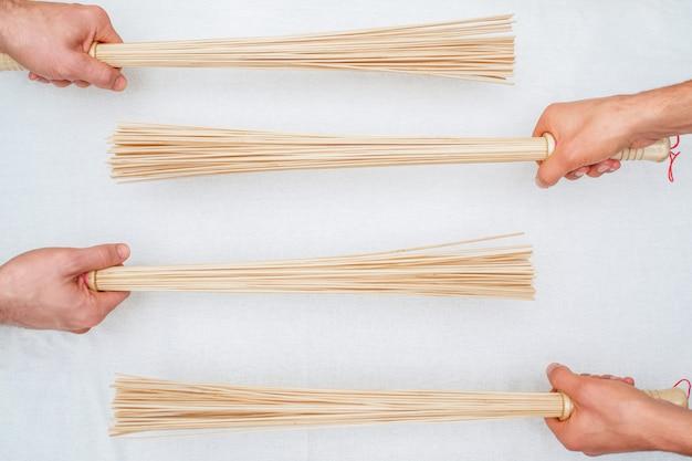 Vassouras de bambu nas mãos do massagista
