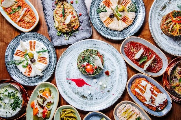 Vasta seleção de alimentos orientais e orientais em pratos rústicos em cima da mesa.