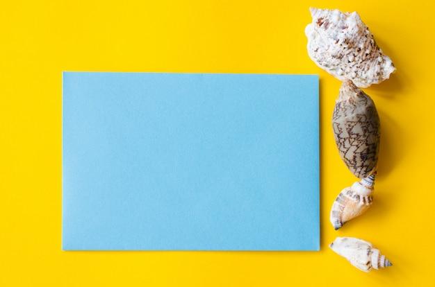 Vazia folha de papel azul sobre fundo amarelo com conchas. fundo de verão.