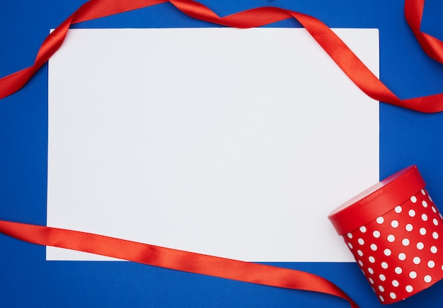 Vazia folha de papel branca e fita torcida de seda vermelha sobre uma superfície azul