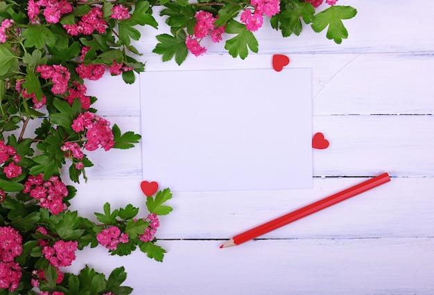 Vazia folha de papel e um lápis de madeira vermelho sobre uma superfície branca