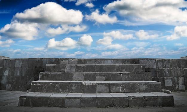 Vazio ao ar livre com céu azul, palco de rock e piso de madeira