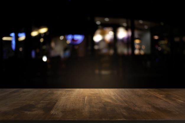 Vazio da mesa de madeira escura em frente ao fundo borrado abstrato da luz do bokeh. pode ser usado para exibir ou montar seus produtos. insira a exibição do produto