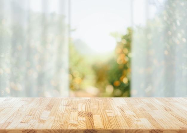 Vazio da mesa de madeira no borrão jardim abstrato com luz solar e janela de cortina, exposição do produto, pronto para montagem do produto.