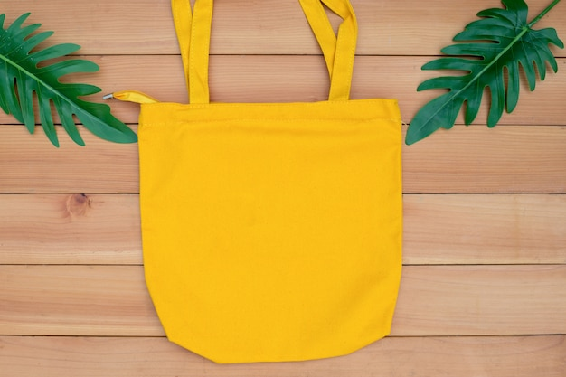 Vazio do modelo do saco da compra de pano de tela da lona da sacola no backgroung de madeira.