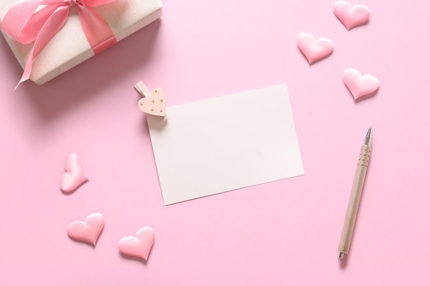 Vazio em branco para cartão de dia dos namorados com presente e corações românticos rosa sobre fundo rosa. cartão com espaço de cópia.