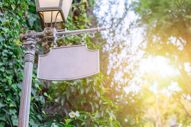 Vazio loja banner placa de metal antigo estilo retro com luz solar de árvore de jardim