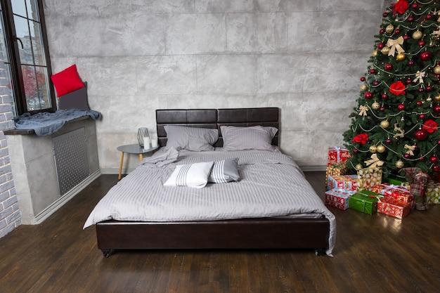 Vazio moderno e ruim em uma sala com um peitoril da janela com um cobertor e uma árvore de natal com presentes