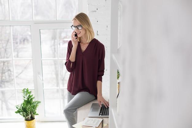 Vê você. mulher de negócios muito alegre usando laptop e falando ao telefone