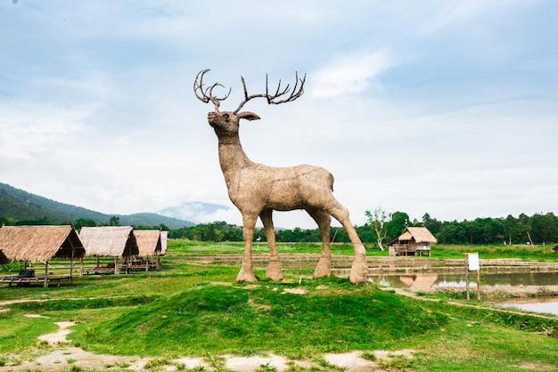 Veado de madeira gigante no campo de arroz
