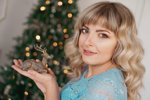 Veado de madeira nas mãos de uma jovem loira. mulher feliz se preparando para o ano novo
