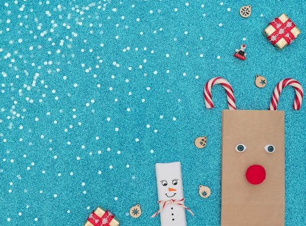 Veado de natal feito de bolsa artesanal e bastões de natal com caixas de presente de boneco de neve e enfeites em fundo azul