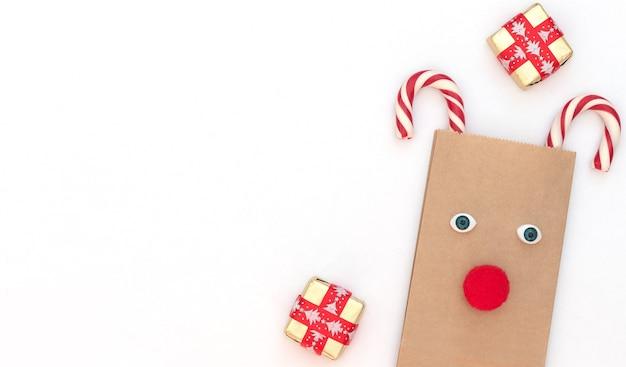 Veado de natal feito de bolsa artesanal e duas bengalas de natal com caixa de presente em branco.