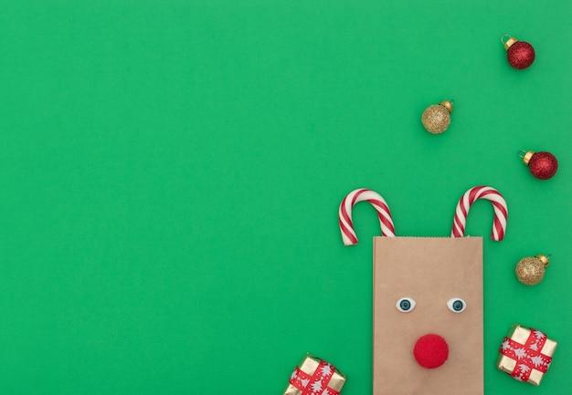 Veado de natal feito de sacola artesanal e duas bengalas de natal com caixas de presente e bolas de natal em fundo verde