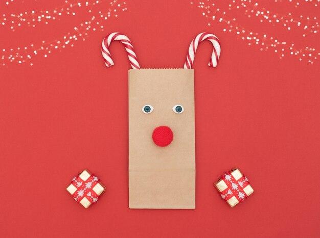 Veado de natal feito de sacola de compras e duas bengalas de natal com caixas de presente em fundo vermelho