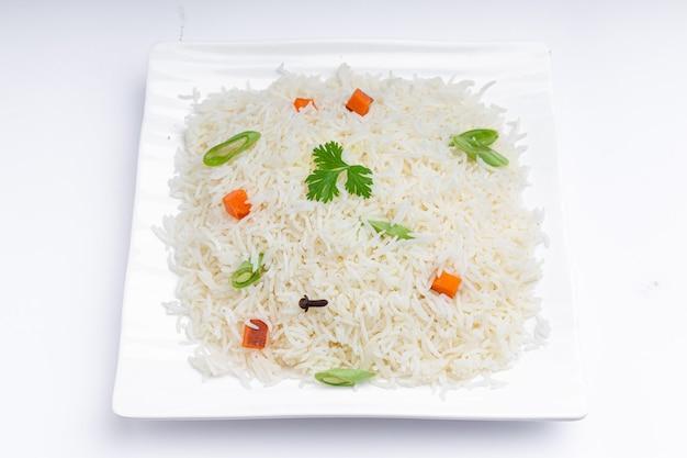 Veg pulao feito com arroz basmati, vegetais e temperos dispostos em talheres brancos quadrados