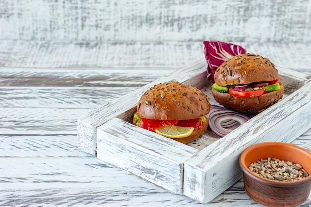 Vegan de hambúrguer caseiro cozido na hora e com salmão em fundo de madeira. alimentos orgânicos hralthy.