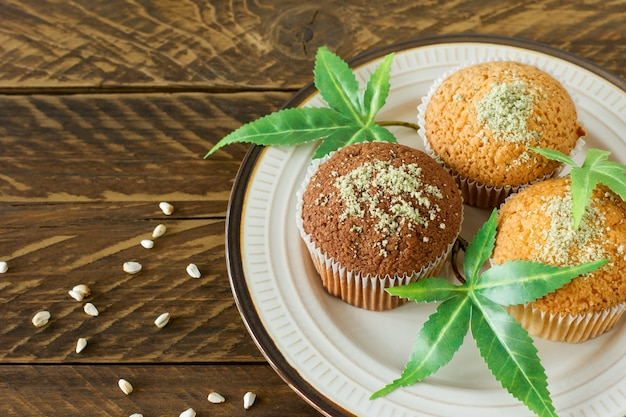 Vegan saudável e saborosa e muffins sem glúten cobertos com sementes de cânhamo em um prato branco na mesa de madeira. queques de bolinho de maconha com folhas de cannabis.