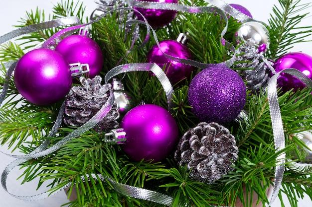 Vegetação de natal com cones de glitter prata e enfeites roxos