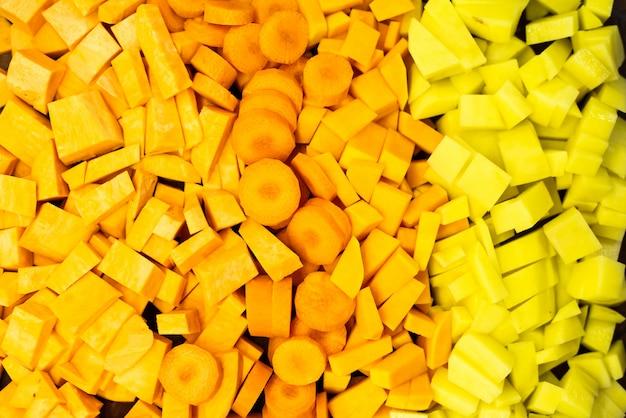 Vegetais alaranjados cortados, cenouras e abóboras, coloridas.