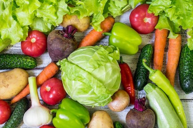 Vegetais coloridos diferentes por todo o lado na tabela no frame cheio. alimentação saudável