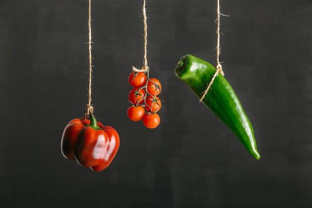 Vegetais coloridos, pimentões e tomates, suspensos por uma corda contra um fundo preto