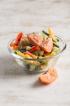 Vegetais congelados. mistura de legumes, vagem e couve-flor em uma tigela de vidro sobre um fundo claro.
